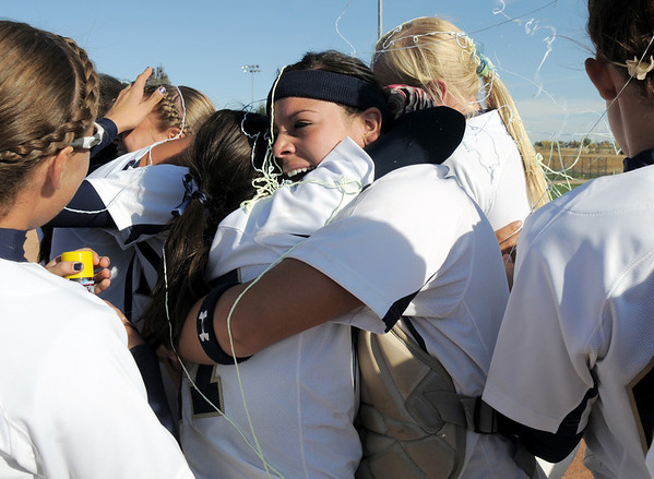 Legacy's catcher Buggs Torrez hugs Shae Rodriguez after winning their fourth state 5A softball championship against Rock Canyon on Saturday at the Aurora Sports Complex. Legacy defeated Rock Canyon 5-2.<br /> <br /> October 23, 2010<br /> staff photo/David R. Jennings