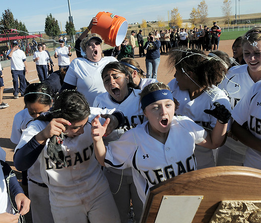 Legacy players react as coach Dawn Gaffin has a bucket of water tossed on her after winning the state 5A softball championship against Rock Canyon on Saturday at the Aurora Sports Complex. Legacy defeated Rock Canyon 5-2.<br /> <br /> October 23, 2010<br /> staff photo/David R. Jennings