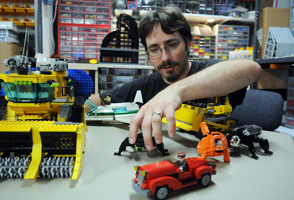 Duane Hess puts a Lego bug, along with other pieces he built with Legos, in a display at his home studio. Hess belongs to a local Lego club.<br /> Sept. 2, 2009<br /> staff photo/David R. Jennings