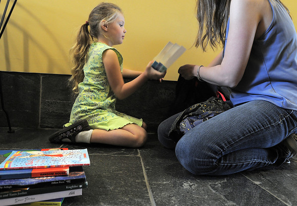 Madeleine Fernandez, 6, helps her mother, Erin, look choose books to buy at the Broomfield Library Friends book sale at the Mame Doud Eisenhower Public Library on Saturday.  <br /> March 31, 2012 <br /> staff photo/ David R. Jennings