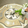 David Floyd, 2, plays on the North metro Fire Rescue emblem on the floor of the headquarters, on Tuesday, after Broomfield Police Sergeant Neil Martinez was presented with the North Metro Fire Rescue District Citizen Life Saving Award for saving the life of Floyd last December.<br /> January 18, 2011<br /> staff photo/David R. Jennings