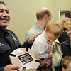 Broomfield Police Sergeant Neil Martinez holds his North Metro Fire Rescue District Citizen Life Saving Award while David Floyd, 2, who Martinez saved, looks at the plaque with his mother Rosemary at North Metro Headquarters on Tuesday<br /> January 18, 2011<br /> staff photo/David R. Jennings