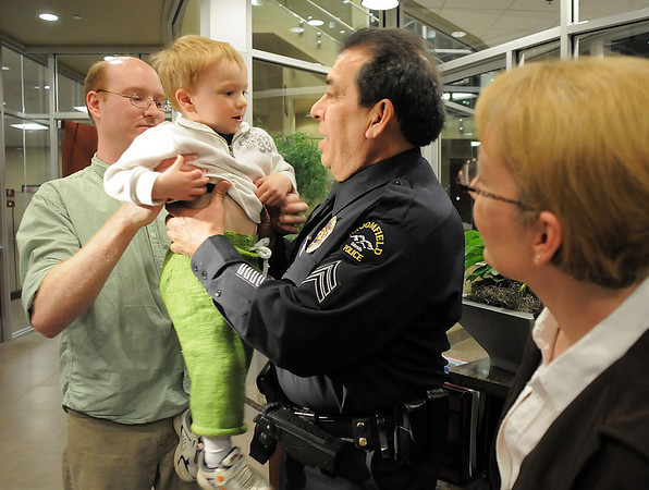 Christopher Floyd, left, hands his son David, 2, to Broomfield Police Sergeant Neil Martinez to hold as David's mother Rosemary watches after Martinez was given a North Metro Fire Rescue District Citizen Life Saving Award at North Metro Headquarters on Tuesday<br /> January 18, 2011<br /> staff photo/David R. Jennings