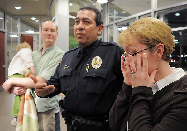 Rosemary Floyd, right, wipes tears while recalling how Broomfield Police Sergeant Neil Martinez saved her son David, 2, who is in the arms of his father Christopher ,left, the ceremony presenting Martinez with the North Metro Fire Rescue District Citizen Life Saving Award at North Metro Headquarters on Tuesday. <br /> January 18, 2011<br /> staff photo/David R. Jennings