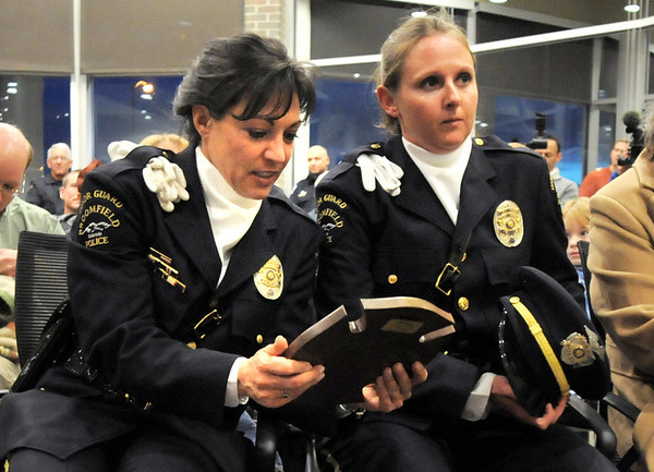 Broomfield Police Officer Angelia Scanga, left, looks at the Citizen Life Saving Award given to officer Kathryn Holsopple, center,  and Sergeant Neil Martinez were presented by the North Metro Fire Rescue District at North Metro Headquarters on Tuesday<br /> January 18, 2011<br /> staff photo/David R. Jennings