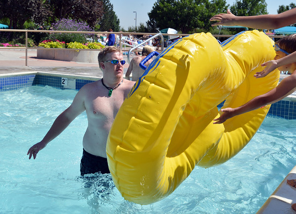 Lifeguard Bryan Harp, 26, hands a tube to the awaiting arms of children at The Bay Aquatic Center on Friday.<br /> <br /> July 13, 2012<br /> staff photo/ David R. Jennings