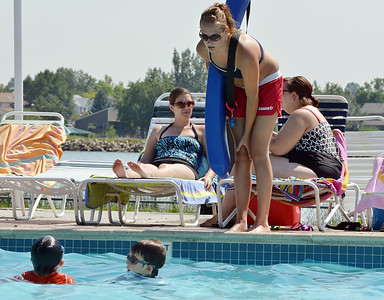 Lifeguard Alissa Johnson, 18, talks to a couple of swimmers in the pool at The Bay Aquatic Center on Friday.  July 13, 2012 staff photo/ David R. Jennings