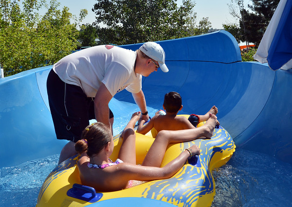 Lifeguard Bryan Harp starts children down the tube slide at The Bay Aquatic Center on Friday.<br /> <br /> July 13, 2012<br /> staff photo/ David R. Jennings