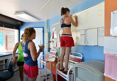 Megan Claussen, 20, stands on a chair to log which station she will begin her lifeguard duties  at The Bay Aquatic Center on Friday.  July 13, 2012 staff photo/ David R. Jennings