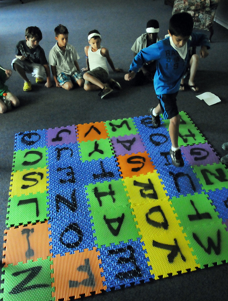 Neil Walia, 8, right, jumps from letter to letter spelling a word as the class watches during Wednesday's Jump Start Literacy Camp at Presbyterian Church of Broomfield.<br /> July 21, 2010<br /> Staff photo/ David R. Jennings