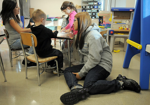 Sophomore Lexis Aragon sits on the floor with Brendan McNeal, 2 1/2, left, during the Little Eagles Playschool child development class at Broomfield High School on Wednesday. <br /> October 16, 2011<br /> staff photo/ David R. Jennings