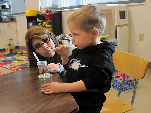 Brendan McNeal, 2 1/2, eats a snack with sophomore Lexis Aragon during the Little Eagles Playschool child development class at Broomfield High School on Wednesday. <br /> October 16, 2011<br /> staff photo/ David R. Jennings