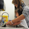 Grace Zechmann, 2 1/2, gets her hands washed with the help of sophomore Lexis Aragon during the Little Eagles Playschool child development class at Broomfield High School on Wednesday. <br /> October 16, 2011<br /> staff photo/ David R. Jennings