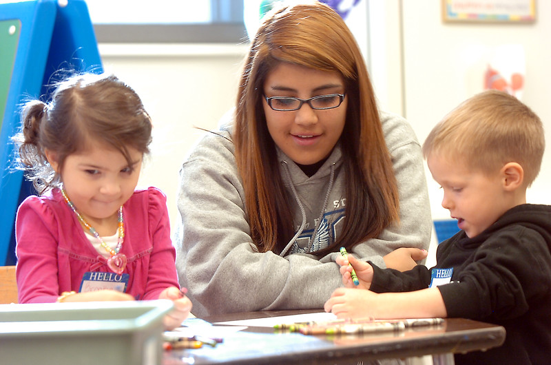 Sophomore Lexis Aragon, center, watches Brooke thurman, 3 1/2. left, and Brendan McNeal, 2 1/2,  color during the Little Eagles Playschool child development class at Broomfield High School on Wednesday. <br /> October 16, 2011<br /> staff photo/ David R. Jennings