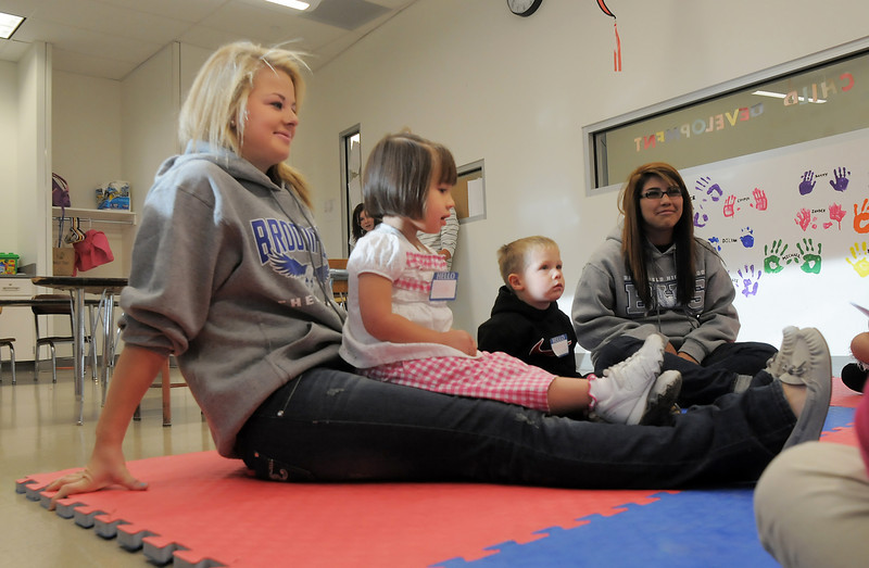 Grace Zechmann, 2 1/2, sits on the lap of sophomore Maddie Elliott during the Little Eagles Playschool child development class at Broomfield High School on Wednesday. <br /> October 16, 2011<br /> staff photo/ David R. Jennings