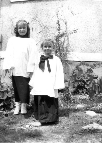 Renee and Susie Kozisek, dressed for the  Methodist Church choir, pose in front of Grandma Kozisek's house at 640 Main St, the Kozisek farm.<br /> <br /> courtesy of Renee Kozisek