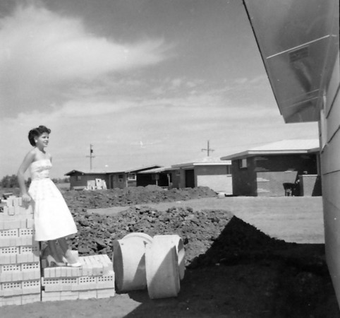 A model, standing on bricks, poses by a house under construction in Broomfield in an undated photo. <br /> <br /> courtesy of the Depot Hill Museum