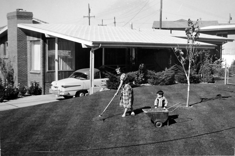 A woman and child rake the lawn of a Broomfield house in an late 1950's photo.<br /> <br /> courtesy of the Depot Hill Museum