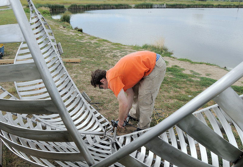 Artist Matt Cartwright grinds pedals on the new replacement Lotus bench at Tom Frost Reservoir on Friday .<br /> <br /> August 26, 2011<br /> staff photo/ David R. Jennings
