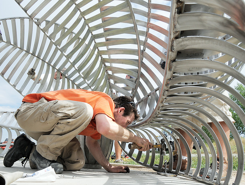 Artist Matt Cartwright places anchor bolts into the concrete to secure the new replacement Lotus bench to anchors at Tom Frost Reservoir on Friday .<br /> <br /> August 26, 2011<br /> staff photo/ David R. Jennings