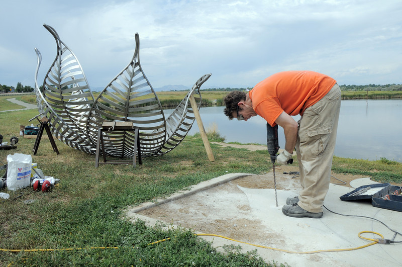 Artist Matt Cartwright drills hole for anchors into the concrete base for the new replacement Lotus bench at Tom Frost Reservoir on Friday .<br /> <br /> August 26, 2011<br /> staff photo/ David R. Jennings