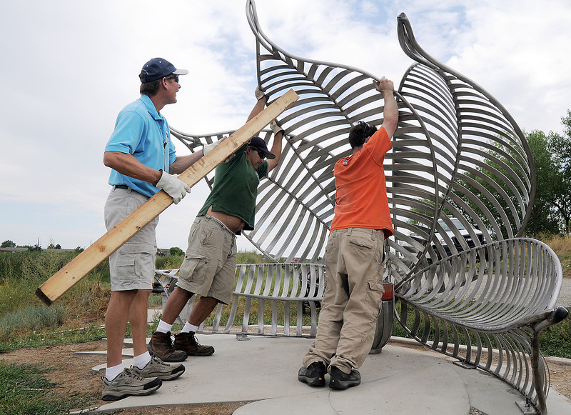 Bill Cooksey, left, Rich Lozano with Broomfield Parks help Artist Matt Carpenter  position the pedals on the new replacement Lotus bench at Tom Frost Reservoir on Friday .<br /> <br /> August 26, 2011<br /> staff photo/ David R. Jennings