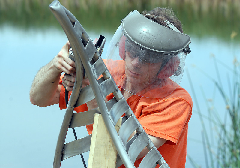 Artist Matt Cartwright grinds the tip of a pedal on the new replacement Lotus bench at Tom Frost Reservoir on Friday .<br /> <br /> August 26, 2011<br /> staff photo/ David R. Jennings