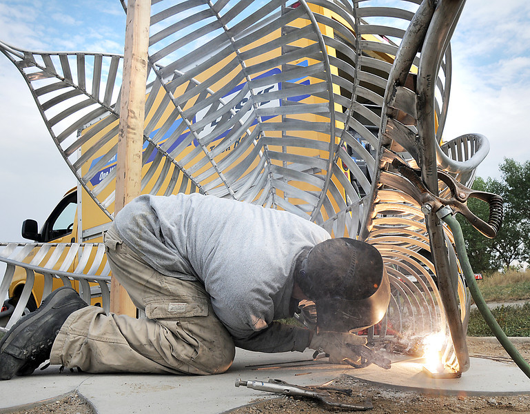 Artist Matt Cartwright welds a new replacement Lotus bench onto anchors in the concrete at Tom Frost Reservoir on Friday .<br /> <br /> August 26, 2011<br /> staff photo/ David R. Jennings