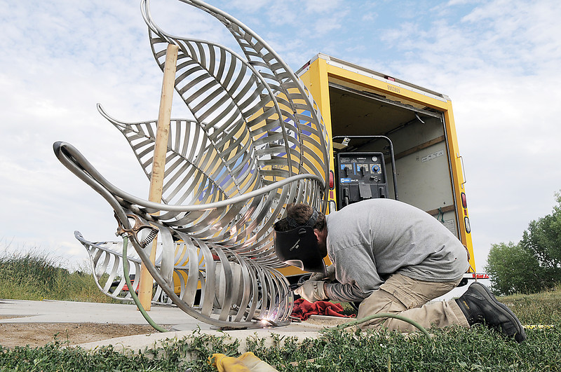 Artist Matt Cartwright welds the new replacement Lotus bench to anchors in the concrete at Tom Frost Reservoir on Friday .<br /> <br /> August 26, 2011<br /> staff photo/ David R. Jennings