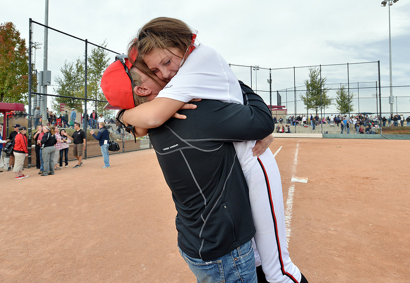 Cassidy Smith  is hugged by homer coach Mark King after Loveland won the state 5A softball championship game against Dakota Ridge on Saturday at Aurora Sports Park.<br /> October 20, 2012<br /> staff photo/ David R. Jennings