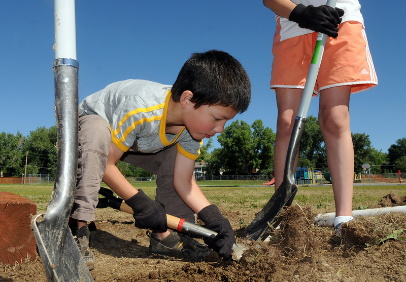 Gabriel Staley, 5, helps dig a hole for water for the garden installed by Lowe's employees at Birch Elementary School on Wednesday.<br /> <br /> August 11, 2010<br /> Staff photo/ David R Jennings