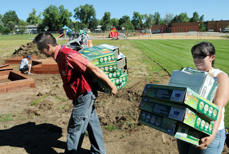 Lowe's store manager Brandon Williams, left, and employee Vanessa Montes carry border material for the garden at Birch Elementary School being installed by Lowe's employees on Wednesday.<br /> <br /> August 11, 2010<br /> Staff photo/ David R Jennings
