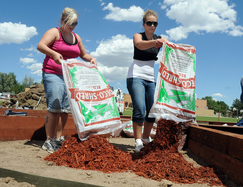 Lowe's employees Amanda Snodgrass, left, and Kati Dyer empty bags of wood chips for the garden being built by Lowe's employees at Birch Elementary School on Wednesday.<br /> <br /> August 11, 2010<br /> Staff photo/ David R Jennings