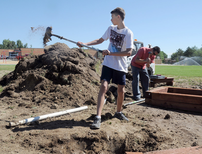 Nick Staley, 14, helps dig a hle for the irrigation system for the garden being installed by Lowe's employees at Birch Elementary School on Wednesday.<br /> <br /> August 11, 2010<br /> Staff photo/ David R Jennings