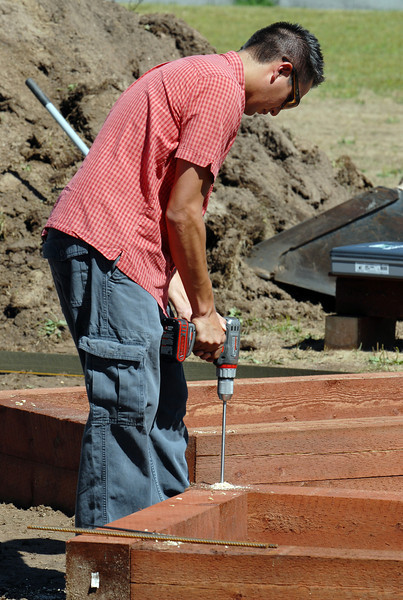 Brandon Williams, Lowe's store manager, drills holes in the wood boxes for the garden being installed by Lowe's employees at Birch Elementary School on Wednesday.<br /> <br /> August 11, 2010<br /> Staff photo/ David R Jennings