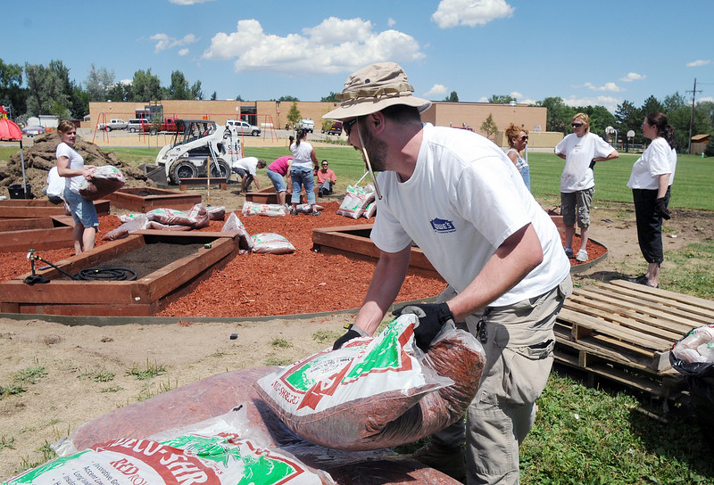 Lowe's employee Bill Plaugher carries a bag of wood chips while helping install a garden at Birch Elementary School on Wednesday.<br /> <br /> August 11, 2010<br /> Staff photo/ David R Jennings