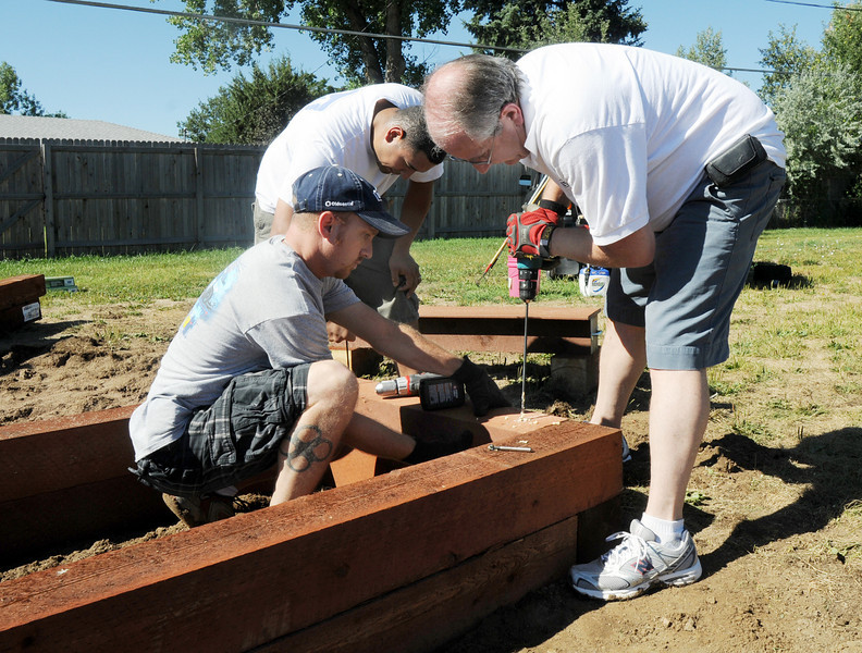 Lowe's employees Brett German, left, Juan Gomez and Randy Miller dril holes to anchor the timber boxes while installing a garden by Lowe's employees at Birch Elementary School on Wednesday.<br /> <br /> August 11, 2010<br /> Staff photo/ David R Jennings