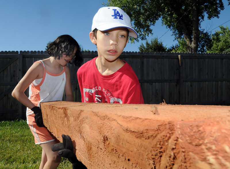 Samuel Staley, 10, right, and his sister Amaris, 10, help carry a log for   a garden being installed by Lowe's employees at Birch Elementary School on Wednesday.<br /> <br /> August 11, 2010<br /> Staff photo/ David R Jennings