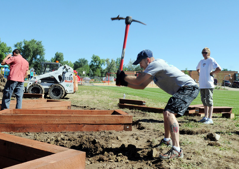 Lowe's employee Brett German uses a pick to dig up a block of concrete while helping install a garden at Birch Elementary School on Wednesday.<br /> <br /> August 11, 2010<br /> Staff photo/ David R Jennings