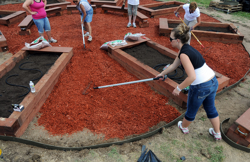 Lowe's employees spread wood chips in the garden at Birch Elementary School being installed by Lowes on Wednesday.<br /> <br /> August 11, 2010<br /> Staff photo/ David R Jennings