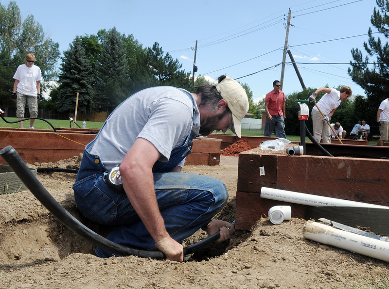 Dale Steckman, Lowe's plumbing specialist, works on the water lines for the garden being install by Lowe's employees at Birch Elementary School on Wednesday.<br /> <br /> August 11, 2010<br /> Staff photo/ David R Jennings