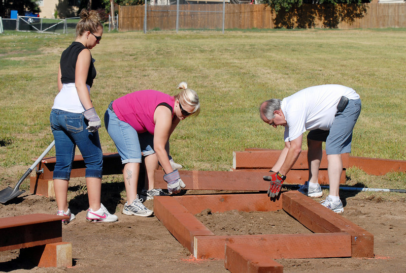 Lowe's employees Kati Dyer, left, Amanda Snodgrass and Randy Miller build a timber box for the garden being installed at Birch Elementary School on Wednesday.<br /> <br /> August 11, 2010<br /> Staff photo/ David R Jennings