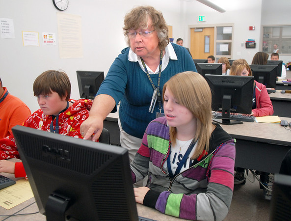 Judy Kurtz, gives instructions to Lori Thayer, right, who is writing an essay on being mature using MY Access! program by Vantage Learning during Kurtz's 10th grade world studies class on Tuesday. Vantage Learning gave a $300,200.00 grant to Adams 12 schools for the program. <br /> Sept. 22, 2009<br /> Staff photo/David R. Jennings