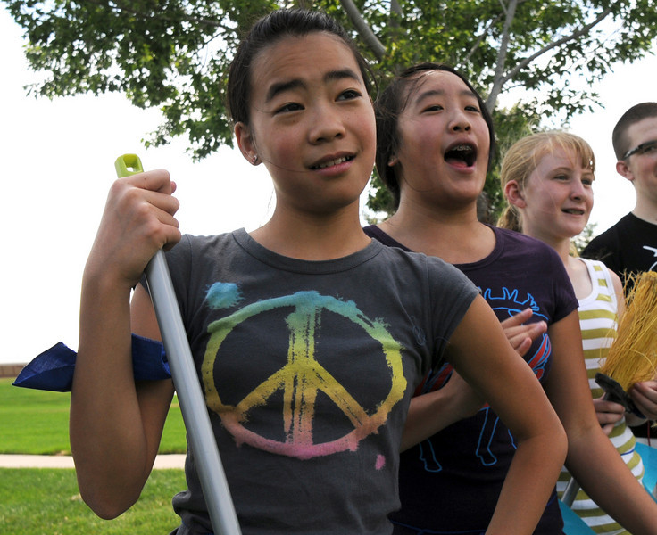 Nichole Mah, 11, left, and Jennifer Mah, 11, with Megan Martin, 11, cheer for their friends playing a match during Wednesday's 2010 Quidditch Cup in celebration of Harry Potter at Community Park.<br /> July 21, 2010<br /> Staff photo/ David R. Jennings