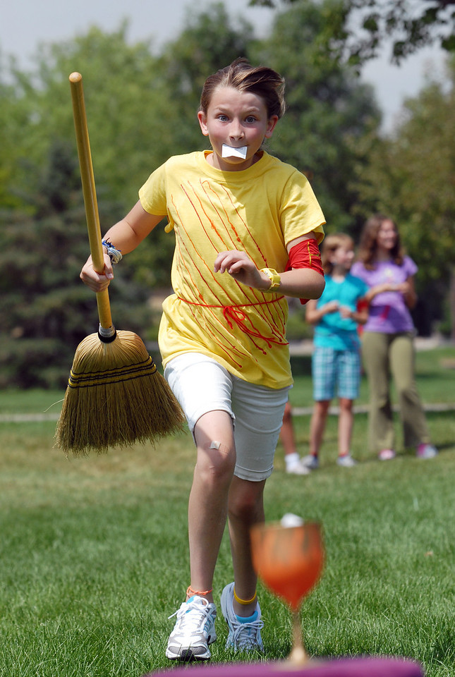Gripping a piece of paper in her mouth, Katie Sanko, 11, runs to place her name in the cup for a game during Wednesday's 2010 Quidditch Cup in celebration of Harry Potter at Community Park.<br /> July 21, 2010<br /> Staff photo/ David R. Jennings