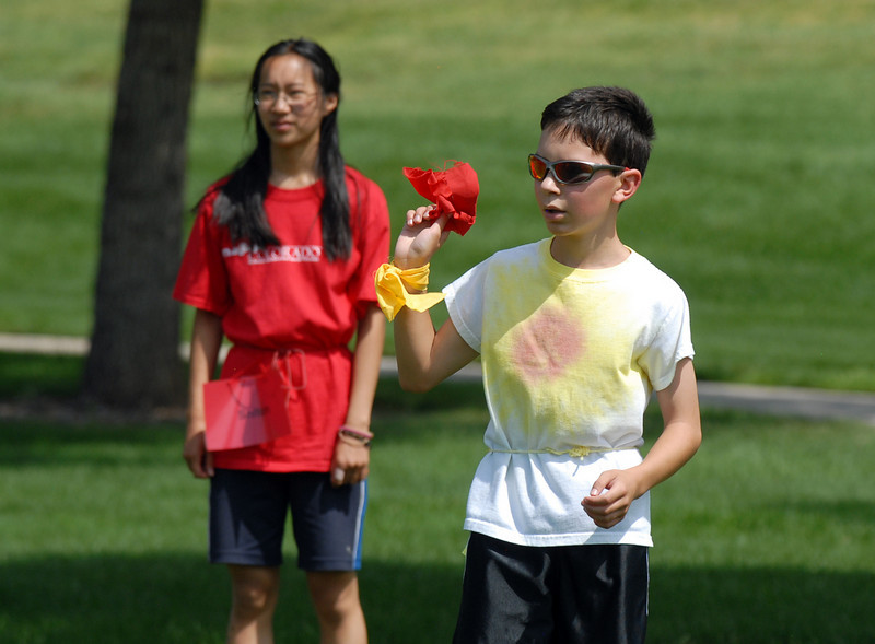Antonio Cabrera, 11, right, holds the flag to signal he caught the Gryffindor's snitch Victoria Zheng, 14, left,  to win the game for Hufflepuff during Wednesday's 2010 Quidditch Cup in celebration of Harry Potter at Community Park.<br /> July 21, 2010<br /> Staff photo/ David R. Jennings
