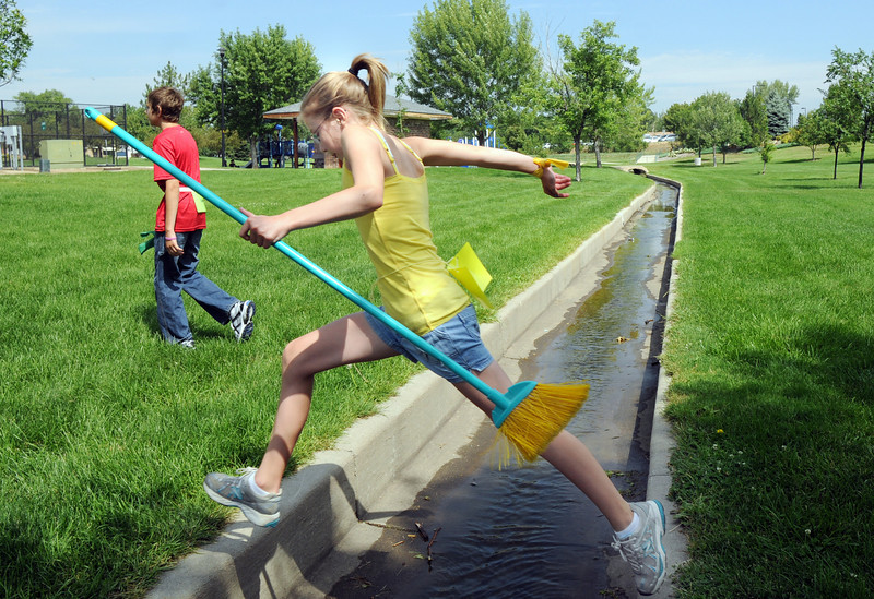 Meghan Brozovich, 11, jumps over a drainage channel with her broom after playing a Quidditch match for the Hufflepuff team during Wednesday's 2010 Quidditch Cup in celebration of Harry Potter at Community Park.<br /> July 21, 2010<br /> Staff photo/ David R. Jennings