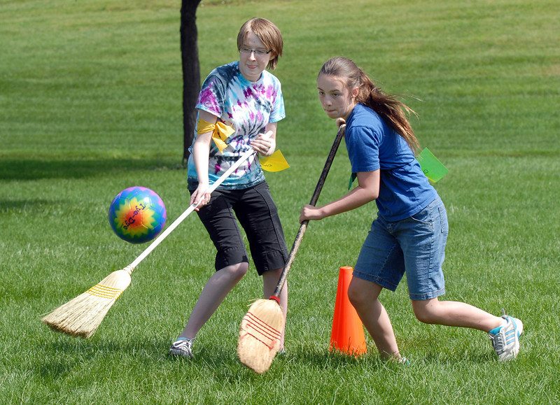 Kelsey Kalmbach, 16, left, Hufflepuff, and Kali Zack, 12, Slytherin, fight to control the quaffle with their brooms during Wednesday's 2010 Quidditch Cup in celebration of Harry Potter at Community Park.<br /> July 21, 2010<br /> Staff photo/ David R. Jennings