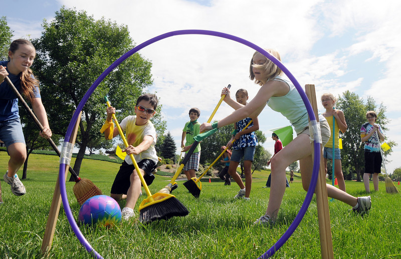 Slytherins Kali Zack, 12, left, and Lexi Brozovich, 12,  right, fight to sweep the quaffle ball through the hoop past Hufflepuff's Antonio Cabrera, 11, to score  during Wednesday's 2010 Quidditch Cup tournament on the pitch of Community Park.<br /> <br /> July 21, 2010<br /> Staff photo/ David R. Jennings