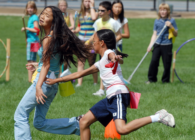 Hufflepuff's snitch, Kaili Mouscher, 13, left, tries to out run Gryffindor's seeker, Monica Mah, 11, during Wednesday's 2010 Quidditch Cup in celebration of Harry Potter at Community Park.<br /> July 21, 2010<br /> Staff photo/ David R. Jennings